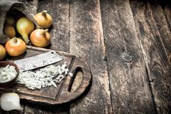 Fresh onion with old hatchet on a cutting board. On a wooden background Royalty Free Stock Photos