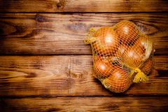 Fresh onion on old wooden burned table or board for background. Stock Image