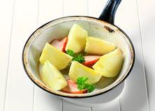 Fresh onion quarters in a pan Stock Photos