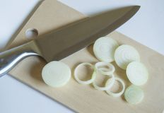 Fresh onion sliced on a cutting Board with a kitchen knife Royalty Free Stock Images