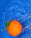 Fresh orange. An orange under a water stream on blue background Royalty Free Stock Images
