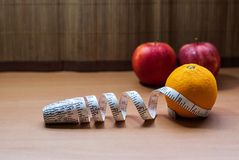 Fresh orange and Apples wrapped with measuring tape Stock Images