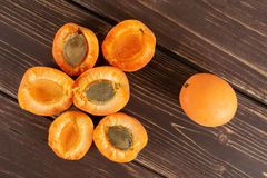 Fresh orange apricot on brown wood. Group of one whole six halves of fresh deep orange apricot with a stone flatlay on brown wood royalty free stock photography
