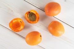 Fresh orange apricot on grey wood. Group of three whole two halves of fresh deep orange apricot with a stone flatlay on white wood stock photos
