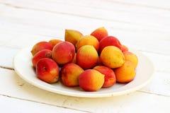 Fresh orange apricots. On white plate on wooden background Stock Photo