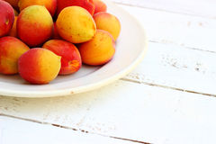Fresh orange apricots. On white wooden background with copy space Royalty Free Stock Images