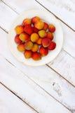Fresh orange apricots. On white wooden background. GMO free food Stock Photo