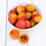 Fresh orange apricots on white wooden background. Summer food Stock Image