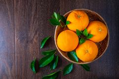 Fresh orange in the basket on wood background top view stock image