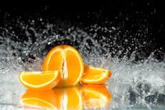 Fresh orange on black background with streaming water on it. Mir Stock Photo