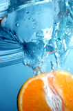 Fresh orange into blue, clear water royalty free stock images