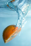 Fresh orange into blue, clear water royalty free stock photography