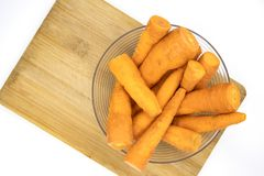 Fresh orange carrot in glass bowl top view photo. Many carrots cleaned for cooking. Healthy dish ingredient. Small carrots on wooden cutting board. Summer Royalty Free Stock Image