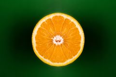 Orange cut in half against green background royalty free stock photos