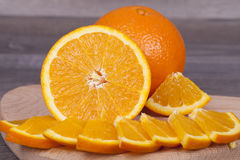 Fresh orange cut into pieces Stock Photos