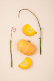 Fresh orange cut pumpkin and dried branches on a light beige pas Royalty Free Stock Photography