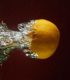 Fresh orange dropped into water Royalty Free Stock Images