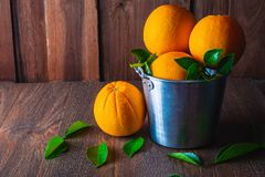 Fresh orange in aluminum basket on wooden background. stock photo