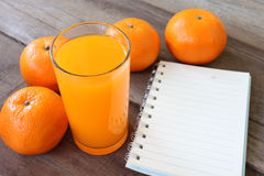 Fresh orange fruit placed on wooden floor and have juice in glas Stock Photo