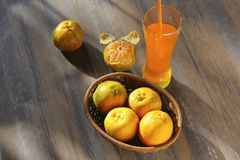 Fresh orange fruits with glass of orange juice. Isolated on wooden background Stock Image