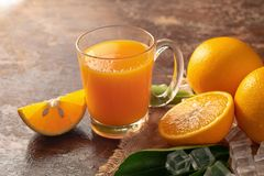 Fresh orange and a glass of orange juice on a wooden table backg. Round stock image