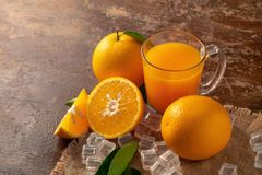 Fresh orange and a glass of orange juice on a wooden table backg. Round stock photography