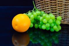 Fresh orange and grape near wooden basket Royalty Free Stock Photo