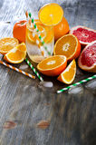 Fresh orange and grapefruits with glass of water and straws samp. Fresh cold citrus drink with fruits on wooden copy space background Royalty Free Stock Photography