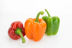 Fresh orange, green and red bell peppers Stock Photography