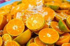 Fresh orange with orange halves on ice. At market royalty free stock image