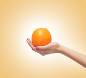 A fresh orange held in beautiful female hands on orange Royalty Free Stock Image
