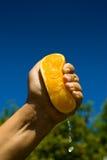 Fresh orange juice. Male hand squeezing an half orange Royalty Free Stock Photos