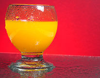 Fresh orange juice. A glass of fresh orange juice with tiny clear drops on its surface. Red background with water splashes on the table Royalty Free Stock Photography