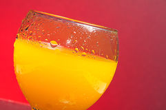 Fresh orange juice. A glass of fresh orange juice with tiny clear drops on its surface. Red background Royalty Free Stock Images