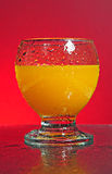 Fresh orange juice. A glass of fresh orange juice with tiny clear drops on its surface. Red background with water splashes on the table Royalty Free Stock Images