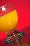 Fresh orange juice. A glass of fresh orange juice with tiny clear drops on its surface. Red background with water splashes on the table Royalty Free Stock Image