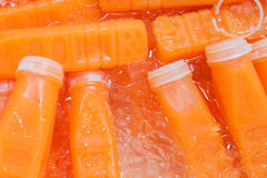 Fresh orange juice bottles on the ice. Stock Images