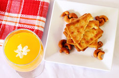 Fresh orange juice with crackers. Presented on a white table with red gingham napkins Stock Photos