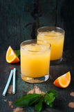 Fresh orange juice with crushed ice and fresh oranges and blue straws on an old vintage exotic background Stock Photo