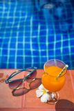 Fresh orange juice drink glass with flower and sunglasses on bor Royalty Free Stock Photos