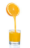 Fresh orange juice flowing from cut orange into the glass. Royalty Free Stock Image