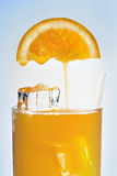 Fresh orange juice is flowing in a glass with ice Royalty Free Stock Images
