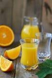 Fresh orange juice. Full glass and jug of orange juice and oranges on wooden table Royalty Free Stock Image