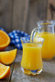 Fresh orange juice. Full glass and jug of orange juice and oranges on wooden table Royalty Free Stock Photos