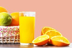 Fresh orange juice in a glass beaker, slices of sliced oranges and basket with oranges isolated on a pink background stock image