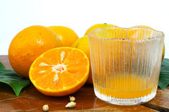 Fresh orange and juice in glass. Half cut and full Fresh orange with juice in the glass Stock Image