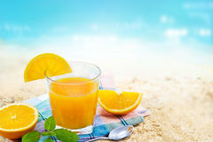 Fresh orange juice with mint on fabric in glass on sand sea beach summer day Royalty Free Stock Photos