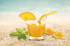 Fresh orange juice with mint in glass on sand sea beach summer day Stock Images