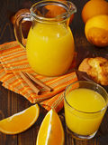 Fresh orange juice and muffins. On a wooden table Royalty Free Stock Photos