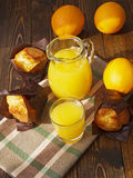 Fresh orange juice and muffins. On a wooden table Stock Photos